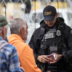 A border official checks a passport at the border crossing between Tijuana and the USA. Omar Martinez | picture alliance | Getty Images