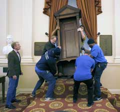 House of Delegates Clerk G. Paul Nardo, left, watches as the circa 1730's original Speaker's chair is put in place inside the Old House Chamber at the State Capitol in Richmond, Va. The speaker's chair, used in Virginia's Colonial House of Burgesses, returned to Richmond on for the first time in more than 80 years. Since the 1930s, the chair has been on a long-term loan to Colonial Williamsburg. (Bob Brown/Richmond Times-Dispatch via AP)