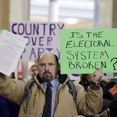 Brock Ervin holds a sign outside the Indiana House chamber before the 11 representatives of the Electoral College gathered on Dec. 19, 2016, in Indianapolis. The U.S. Supreme Court has agreed to hear two cases challenging state attempts to penalize Electoral College delegates who fail to vote for the presidential candidate they were pledged to support. Darron Cummings/AP