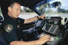 Police officer using computer keyboard in car.