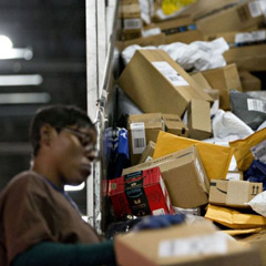 An employee sorts packages at the United Parcel Service Inc. (UPS) Chicago Area Consolidation Hub in Hodgkins, Illinois, U.S., on Tuesday, Dec. 5, 2017. UPS is expecting slight delays in package deliveries through the middle of this week after a surge in e-commerce sales swamped its network in the days after Thanksgiving.