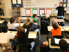 School leaders are key to improving teaching and learning. Picture of teacher with students.