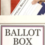 Hand dropping a ballot into a ballot box.