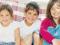 Three Children Sitting on Sofa