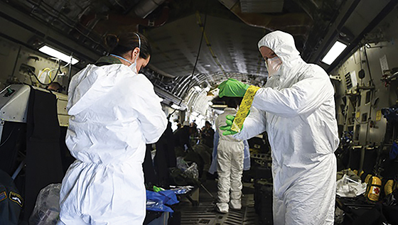 U.S. airmen on board a military aircraft don personal protective equipment as part of training to transport patients with infectious diseases like coronavirus.