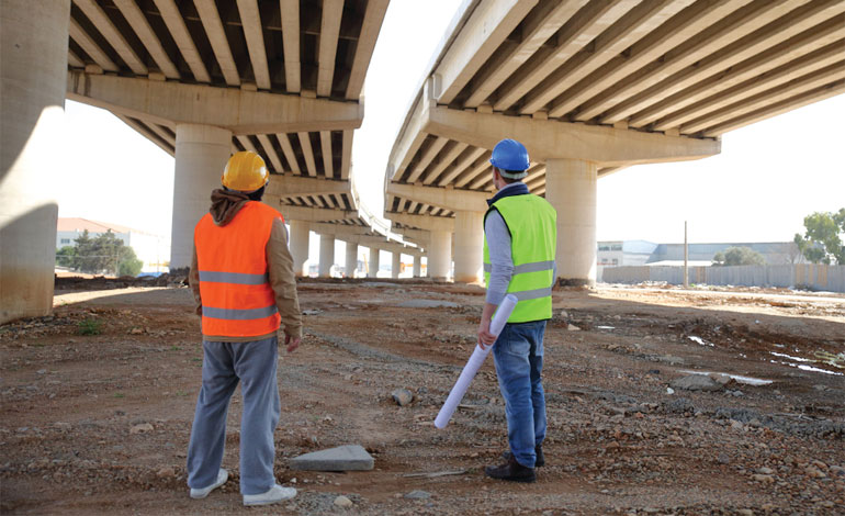 Two men in hard hats inspecting a highway viaduct