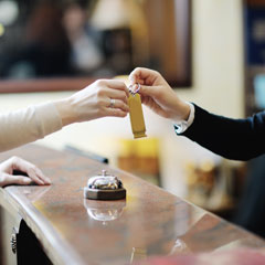 A hotel clerk gives a guest a room key