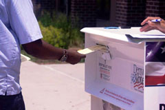 A photograph shows a voter slipping a sealed election ballot into a drop box in Denver, Colorado.