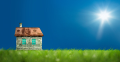 Conceptual image of money house on green landscape.
