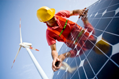Worker installing solar panels with a wind turbine in the background.