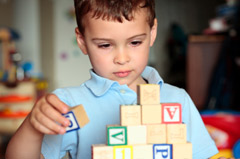 Young boy playing with wooden blocks with letters on them