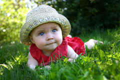 Baby girl crawling in the green grass