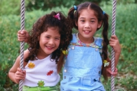 Two young girls sitting on a swing together