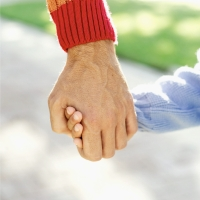 An older adult holding the hand of a younger child