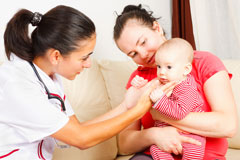 Nurse checking on infant that sits on mothers lap