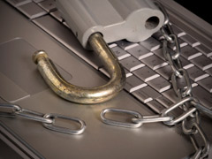 A photo of a an open padlock and broken chain on top of a silver laptop keyboard.