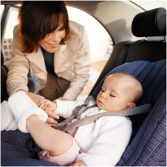 Mother buckling baby in car set photo