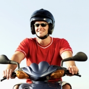 Man wearing helmet riding a motorcycle.