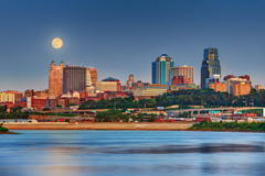 a photo of the Kansas City skyline with a full moon in the sky