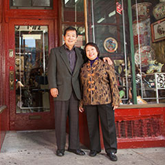 Two people standing in front of a store.