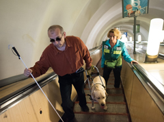 Blind man with service dog going up escalators