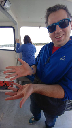 A photo of new Missouri Legislative Librarian, Nathan Elwood. Holding a tiny crab