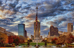 A photo of the skyline of Indianapolis with a large flag pole in the foreground