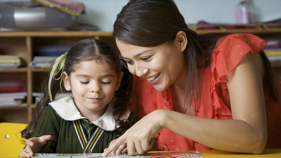 Young girl reading with teacher