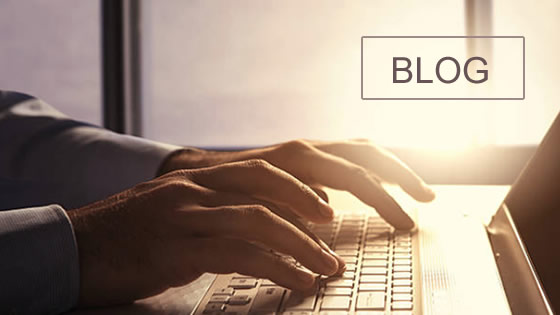 Hands typing on a laptop with the word Blog in a square