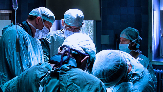 5 doctors in an operating room performing surgery