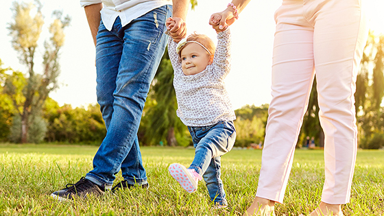 Young child with arms stretched upwards to hold parents hands as they walk.