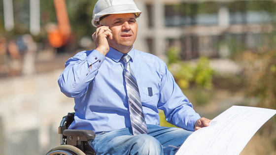 Man in a wheelchair on the phone at a construction site