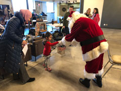A photo of Santa Claus stooping to give a gift to a little girl in a red dress