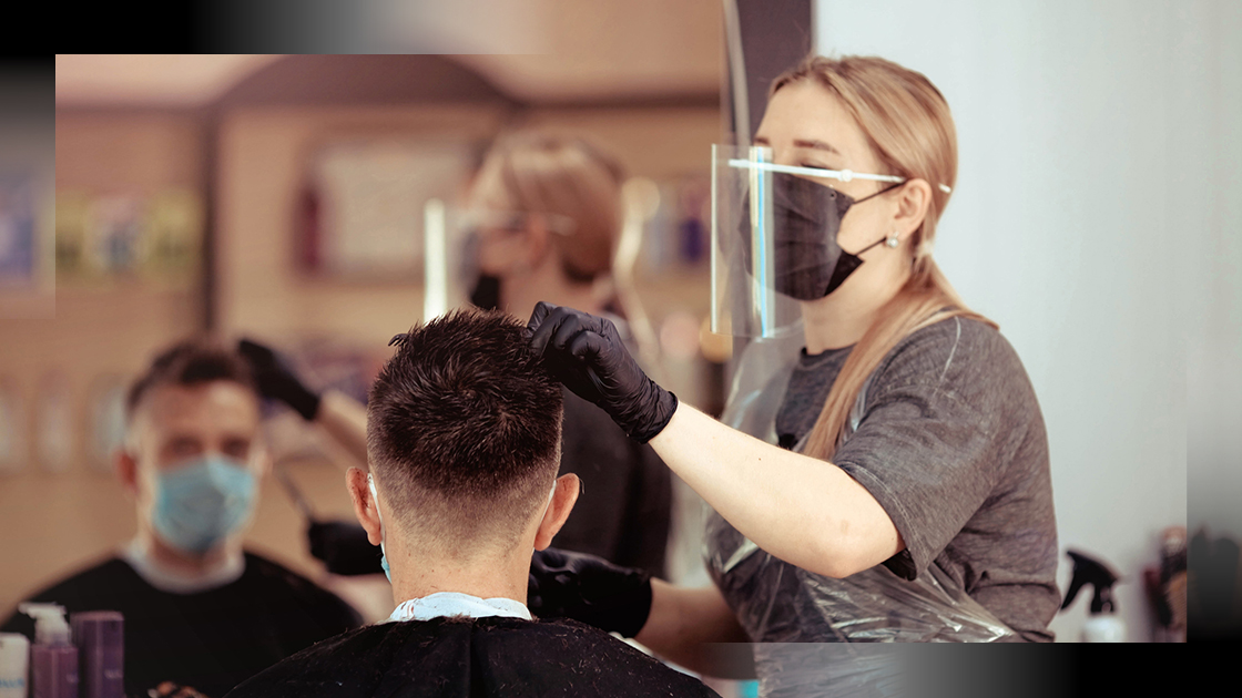 barber cuts hair wearing mask and protective equipment