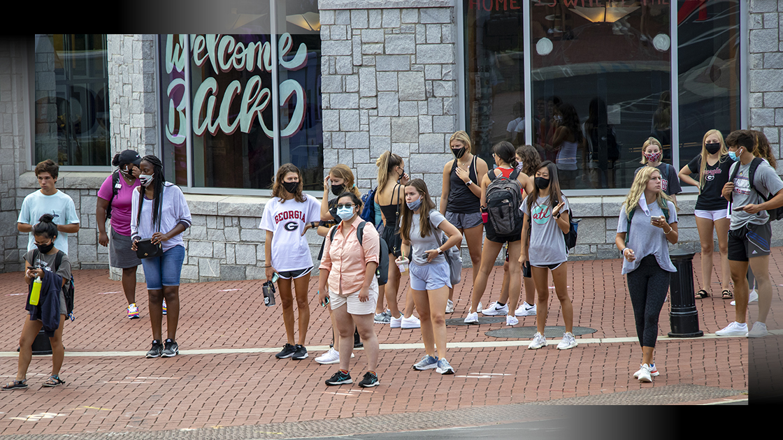 students in protective face masks mingle outside Bolton Dining Commons at the University of Georgia
