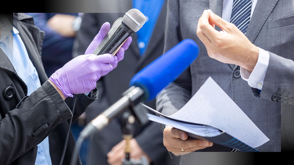 closeup of journalist at a news conference wearing protective gloves and holding a microphone