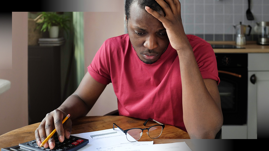 man reacts with concern while looking at bills to be paid
