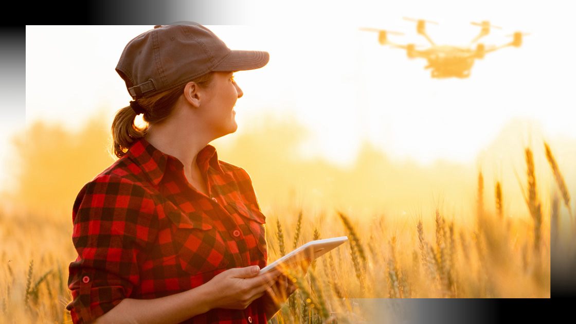 woman standing in open field operating a drone