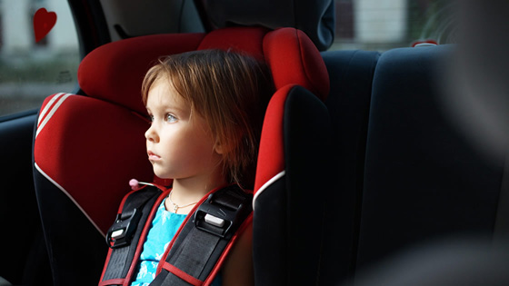 Child in car seat in vehicle.